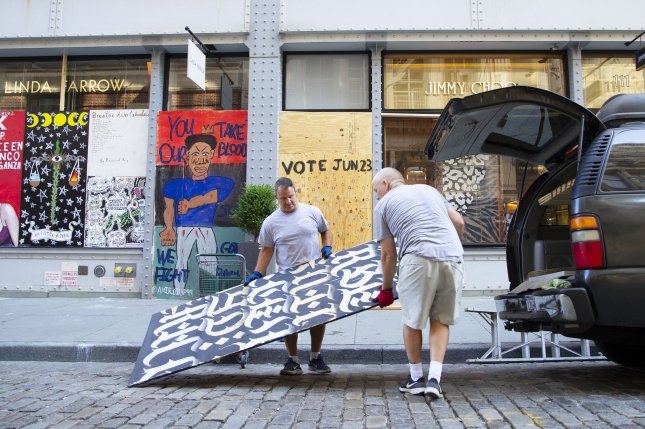 Workers break down the street art painted, boarded up windows of a Jimmy Choo retail store Monday in Manhattan when New York City enters phase 2 of a four-part reopening plan after being closed for 3 months due to COVID-19. Photo by John Angelillo/UPI