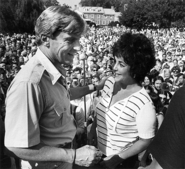 Sen. John Warner, R-Va., and wife Elizabeth Taylor greet thousands of supporters at their annual country supper at the Warner farm in Middleburg, Va., on September 13, 1980. File Photo by Mitch Koppelman/UPI