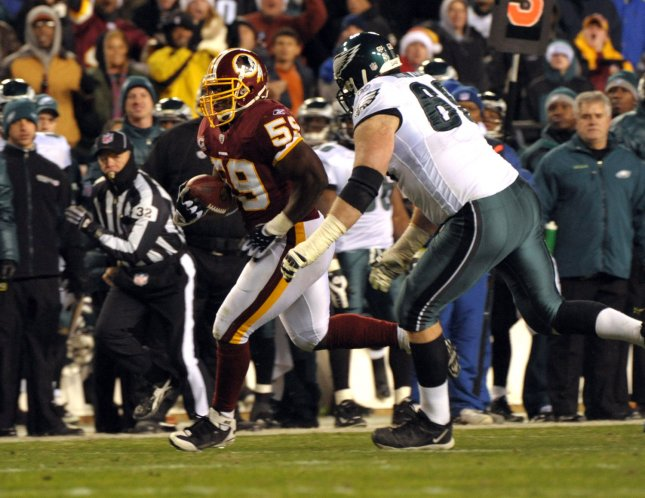 Washington Redskins linebacker London Fletcher is pursued by Philadelphia Eagles tackle Jon Runyan after Fletcher picked up the ball fumbled by Eagles quarterback Donovan McNabb in the third quarter at FedEx Field in Landover, Maryland, on December 21, 2008. The turnover set up a Redskins winning touchdown, with the final score 10-3. (UPI Photo/Roger L. Wollenberg)