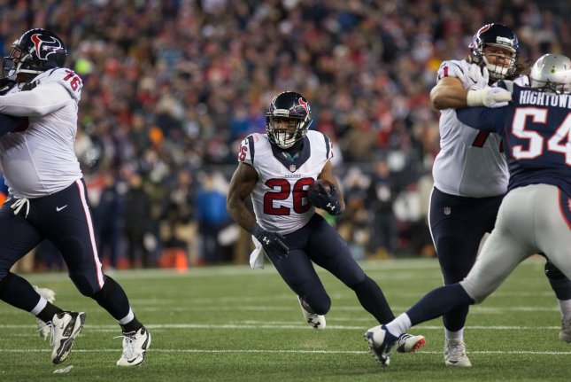 Houston Texans running back Lamar Miller (26) charges into an opening on a carry in the second quarter of the AFC Divisional Round playoff game against the New England Patriots on January 14, 2017 at Gillette Stadium in Foxborough, Massachusetts. Photo by Matthew Healey/UPI
