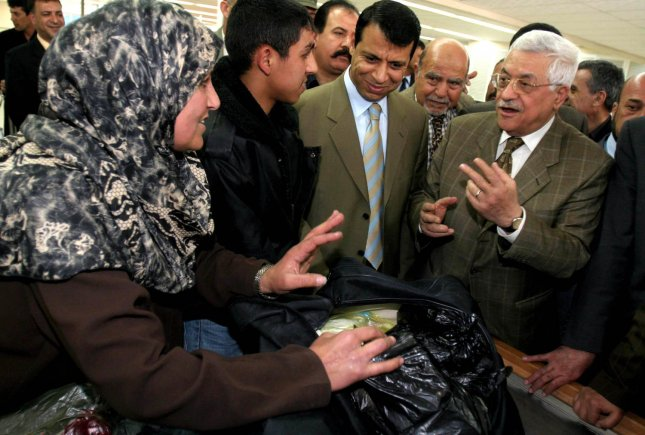 Palestinian leader Mahmoud Abbas (r) talks to travellers during a visit to the Rafah crossing border between Gaza Strip and Egypt, in southern Gaza Strip Sunday on March 19, 2006. Abbas said he would ask Hamas to present its proposed Cabinet, after the militant group failed to bring in moderate parties that might have eased Western threats of a massive aid cutoff. Also seen in the picture is Mohammed Dahlan, a leader of the young Fatah guard, second from right. (UPI Photo/Khalil Hamra, Pool )