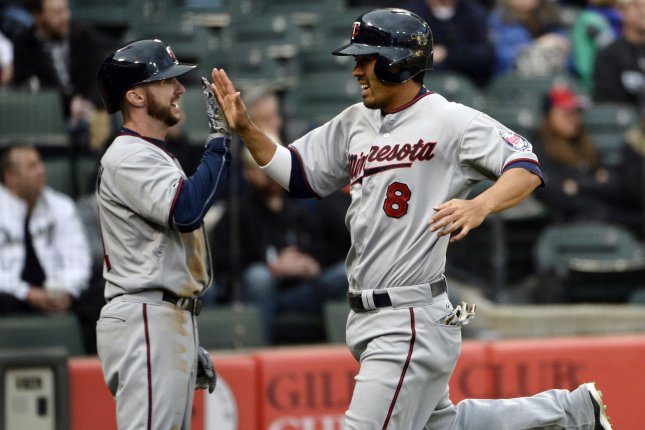Minnesota Twins Kurt Suzuki (R) high fives teammate Shane Robinson. Photo by Brian Kersey/UPI