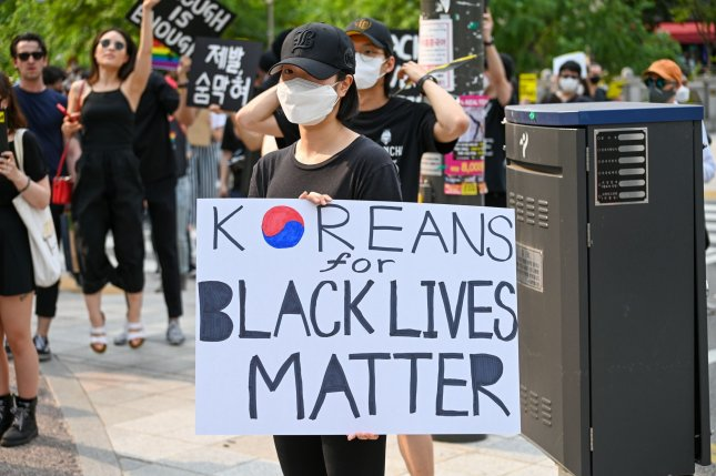 A South Korean demonstrator holds up a sign in support of the Black Lives Matter movement in downtown Seoul on Saturday. Photo by Thomas Maresca/UPI