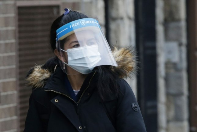 A woman walks on the sidewalk wearing a face mask and face shield in New York City. File Photo by John Angelillo/UPI