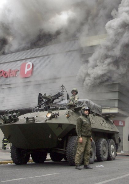 Military officers stand guard at a La Polar retail store in Concepcion, Chile on March 3, 2010, after looters set in on fire last night. Areas of Chile have been devastated and hundreds have died after an 8.8 magnitude earthquake struck the country on February 27. UPI/Carlos Acuna