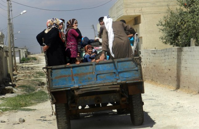 Syrian civilians flee in a vehicle at Houla near Homs, September 9, 2012, government forces shelled a number of areas in northern Syria part of efforts by the regime to target rebel strongholds.Troops used planes to hit several homes in Aleppo, the Syrian Observatory for Human Rights. UPI