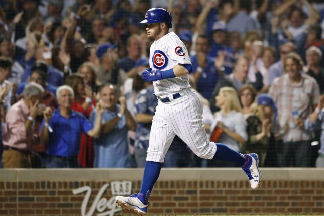 Chicago Cubs center fielder Ian Happ rounds the bases after hitting three-run home run against the Cincinnati Reds in the seventh inning on Friday at Wrigley Field in Chicago. Photo by Kamil Krzaczynski/UPI