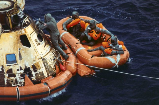 Pararescueman Lt. Clancy Hatleberg closes the Apollo 11 spacecraft hatch as astronauts Neil Armstrong, Michael Collins, and Buzz Aldrin, Jr. await a helicopter pickup from their life raft after they splashed down 900 miles southwest of Hawaii on July 24, 1969. File Photo courtesy NASA