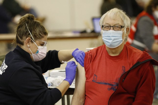 Gerold Goerkzen, of Homerville, receives his COVID-19 vaccine from Lafayette Township Fire EMT Jessica Kulik at the Medina Community Center in Medina, Ohio, in early February. File Photo by Aaron Josefczyk/UPI