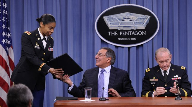 Out-going Defense Secretary Leon Panetta (L) hands the memorandum lifting the ban on women in combat to an aide after signing the document along with Chairman of the Joint Chiefs of Staff Gen. Martin Dempsey, at the Pentagon, in Arlington, Virginia, January 24, 2013. The ruling formalizes a fact that women have been serving and dying on the front lines in Afghanistan and Iraq for over ten years. UPI/Mike Theiler