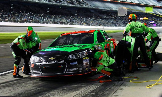 Crew members scramble to repair the car of Danica Patrick after a late race incident at Daytona International Speedway on February 19, 2015 in Daytona Beach, Florida. Photo by Ed Locke/UPI