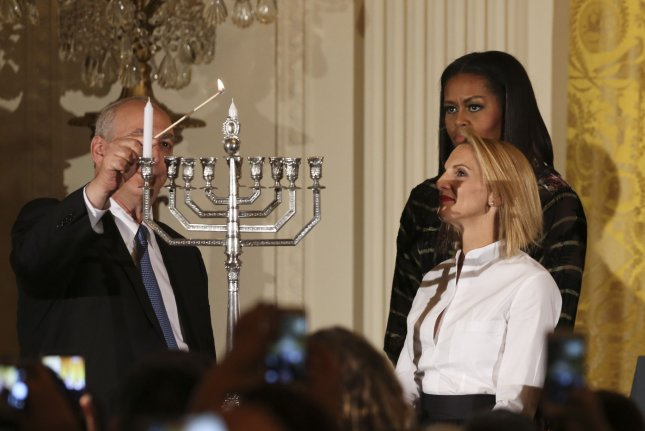 Late Israeli president Shimon Peres' son, Chemi (L), and granddaughter, Mika Almog (R), light the menorah while President Barack Obama (unseen) and first lady Michelle Obama (C) watch during the second Hanukkah reception of the day in the East Room of the White House on Wednesday in Washington, D.C. Pool photo by Aude Guerrucci/UPI