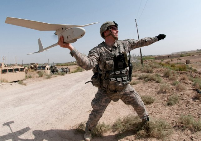 Army 1st Lt. Steven Rose launches an RQ-11 Raven unmanned aerial vehicle near a new highway bridge project along the Euphrates River north of Taqqadum, Iraq on October 9, 2009. UPI/Michael J. MacLeod/U.S. Army