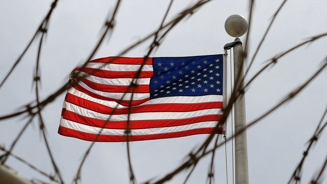 An American Flag is seen through razor wire at a Naval Station in Guantanamo Bay, Cuba on July 8, 2010. UPI/Roger L. Wollenberg