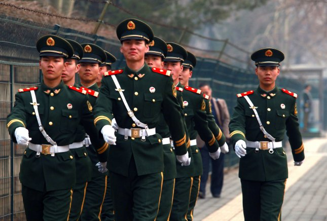 Chinese People's Liberation Army soldiers march through the North Korean Embassy area in Beijing in 2013. Earlier this month, China allowed 13 North Koreans traveling on valid passports to leave the country, which signals a change, according to a U.S. human rights activist. File Photo by Stephen Shaver/UPI
