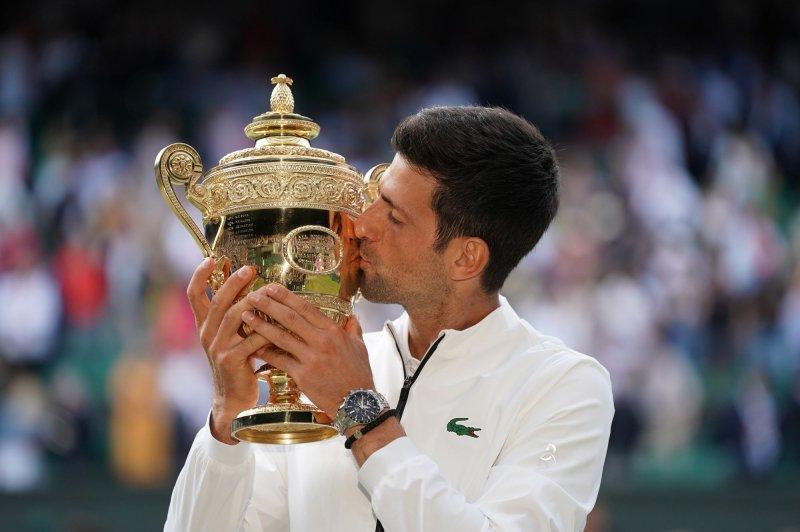 Serbian Novak Djokovic kisses the winners trophy at Wimbledon on Sunday. Photo by Hugo Philpott/UPI