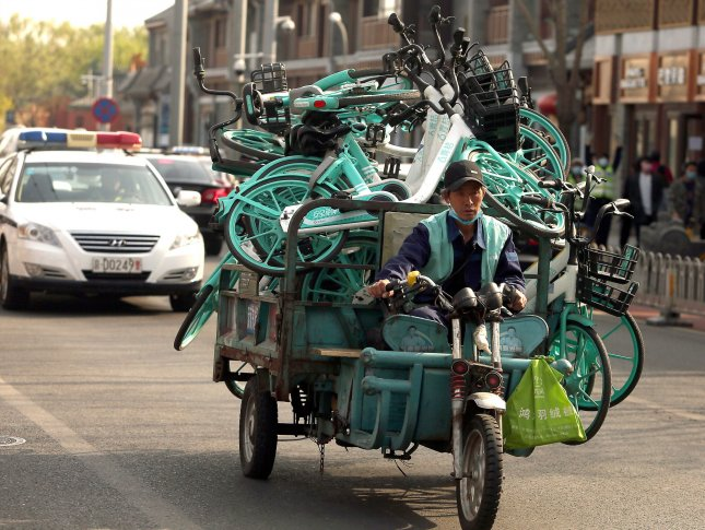 A Chinese worker hauls rental bikes while partially wearing a protective face mask amid reports of a decline in the threat of the Covid-19 virus in Beijing on Tuesday. Photo by Stephen Shaver/UPI