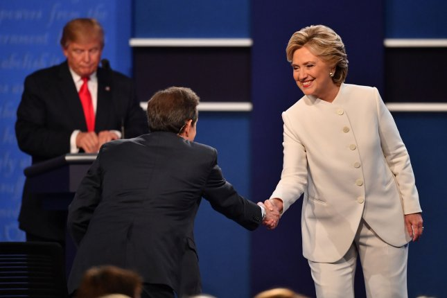 Republican presidential candidate Donald Trump collects himself as Democratic presidential candidate Hillary Clinton shakes hands with moderator Chris Wallace following the third and final debate at the University of Nevada, Las Vegas (UNLV), in Las Vegas, Nev., on Wednesday. Photo by Kevin Dietsch/UPI