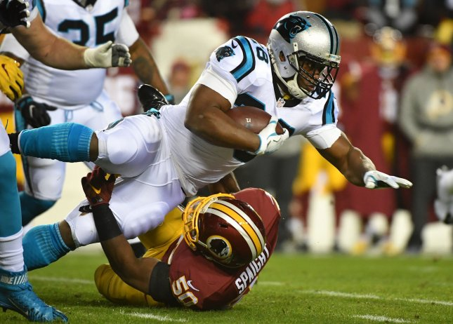 Former Carolina Panthers running back Jonathan Stewart dives for yardage over Washington Redskins outside linebacker Martrell Spaight during their game in 2016. Photo by Kevin Dietsch/UPI