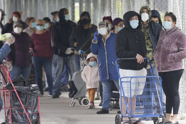 People wearing face masks wait on line for food at a distribution site in New York City Monday. The World Health Assembly on Tuesday approved a measure to probe the origins of the pandemic, which has killed nearly 320,000 worldwide. Photo by John Angelillo/UPI