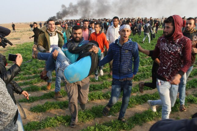 Palestinian protesters carry an injured comrade during clashes with Israeli forces Friday east of the southern Gaza Strip city of Khan Younis following a protest against U.S. President Donald Trump's decision to recognize Jerusalem as the capital of Israel. Photo by Ismael Mohamad/UPI