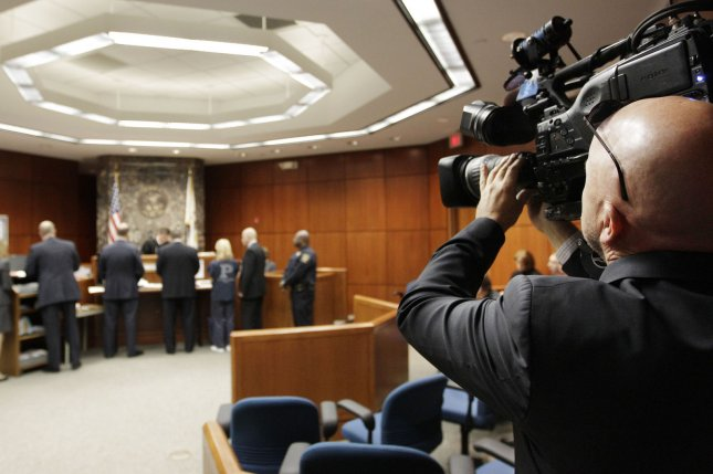 A photojournalist points his camera toward the bench in a DuPage County, Ill., courtroom. The proposedCameras in Courtroom Act would allow, for the first time, hearings before the U.S. Supreme Court to be televised.File Photo by M. Spencer Green/UPI