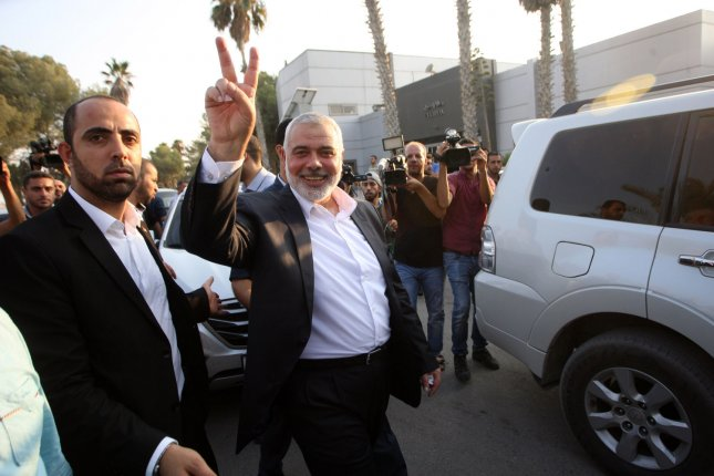 Hamas Chief Ismail Haniyeh flashes the victory gesture upon his arrival on the Palestinian side of the Rafah border crossing, in the southern Gaza Strip on Tuesday. The delegation of the Hamas leadership is returning from Cairo to Gaza after long meetings with the Egyptian government the agreement on reconciliation between Hamas and Fatah. Photo by Ismael Mohamad/ UPI.