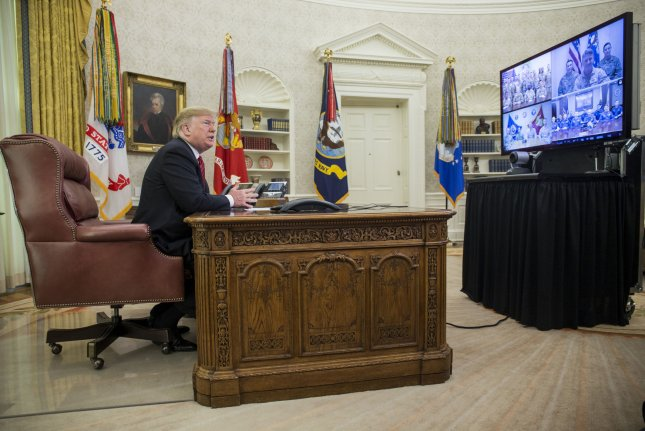President Donald Trump speaks Tuesday to U.S. service members from the Army, Marine Corps, Navy, Air Force and Coast Guard from the Oval Office of the White House. Photo by Zach Gibson/UPI