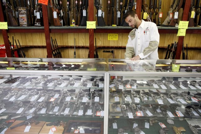 This 2010 file photo shows an employee showing various handguns displayed at G. A. T. Guns in Dundee, Ill. The National Rifle Association, in concert with other gun rights groups and a retailer, sued Friday asking California to declare gun shops essential businesses under Gov. Gavin Newsom's stay-at-home order to prevent the spread of the novel coronavirus. Brian Kersey/UPI