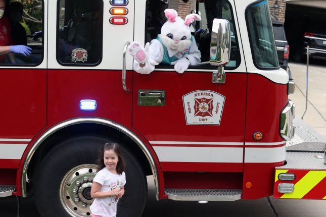 The Easter Bunny waves to children from a Eureka, Mo., fire truck, saying hello to children in Jefferson County neighborhoods on Saturday Photo by Bill Greenblatt/UPI