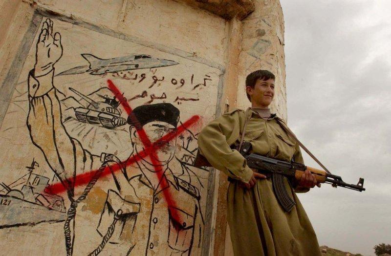 KPP2003040704 - Ghader Karam, Iraq, April 7 (UPI) -- An Iraqi Kurdish peshmerga stand guard in front of destroyed portrait of Saddam Hussein in Ghader Karam Village about 60 KM to City of Kirkuk in Northern Iraq..mk/ak/Ali Khaligh UPI