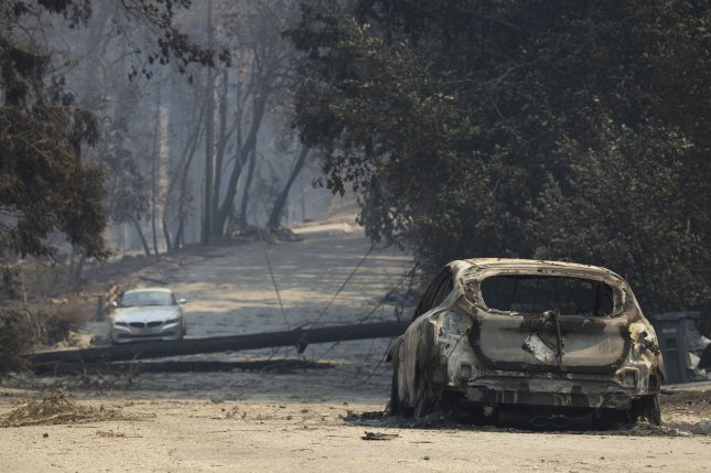 The remains of a burnt vehicle and toppled power pole in Boulder Creek, California amid the CZU Lightning Complex fire. File Photo by Peter DaSilva/UPI