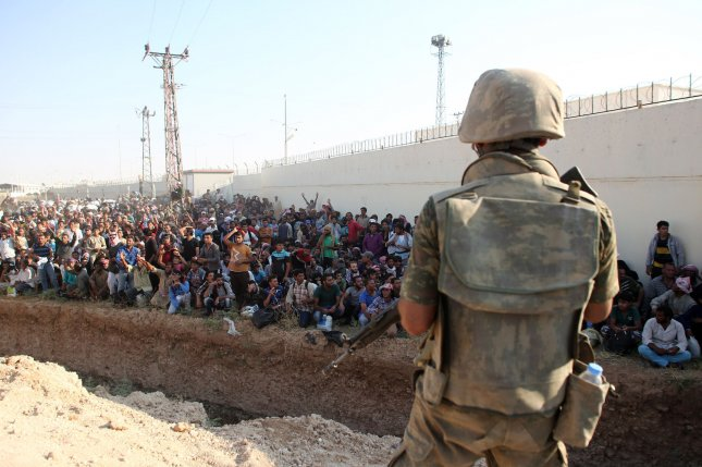 Turkey has vowed to increase border security following an attack on Suruc, a town bordering Syria. Pictured: Turkish soldiers guard while hundreds of Syrian refugees wait at the Syrian side of the border crossing in Akcakale, Sanliurfa province, south-eastern Turkey, June 14 2015. They are trying to cross to the Turkish side as they are fleeing from the fighting between the Kurdish People's Protection Units (YPG) military group and Islamic State. File Photo by Ebrahem Khadir/ UPI