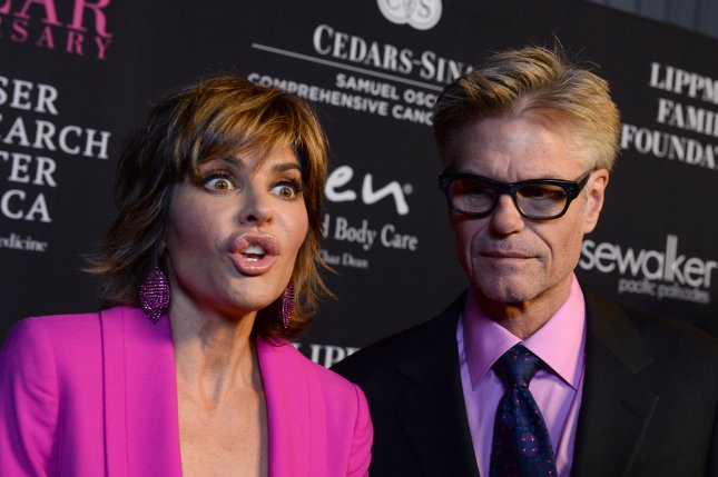 Harry Hamlin (R) and wife Lisa Rinna at the Pink Party for cancer research on October 18, 2014. The couple apologized for the swastika t-shirt the actor wore on Halloween. File photo by Jim Ruymen/UPI