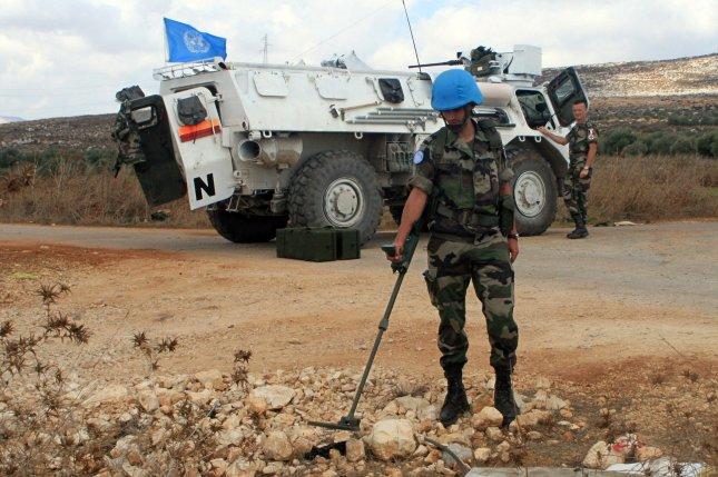 French U.N. peacekeepers look for unexploded cluster bombs on the side of the road near the south Lebanese village of Blat on September 29, 2006. The Pentagon on Thursday said it's delaying its plan to stop using cluster bombs by the beginning of 2019. UPI File Photo