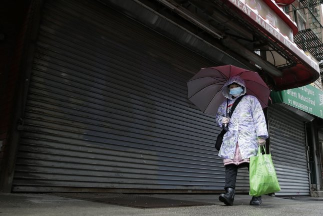 A woman wears a protective mask and gloves as she walks by a series of closed markets and retail stores in the Chinatown section of Manhattan in New York City on Tuesday. Photo by John Angelillo/UPI