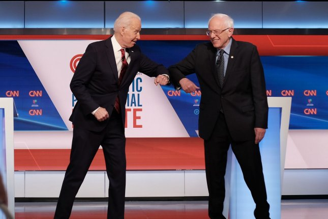 Former Vie President Joe Biden (L) and Vermont Sen. Bernie Sanders bump elbows before a primary debate in Washington, D.C., on March 15, a couple weeks before Sanders dropped out of the race. File Photo by CNN/UPI