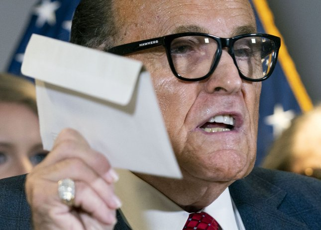 Rudy Giuliani, President Donald Trump's campaign legal advisor, holds an envelope representing mail-in voting as he speaks on the election results, at the Republican National Committee headquarters in Washington, D.C. on Thursday. Photo by Kevin Dietsch/UPI