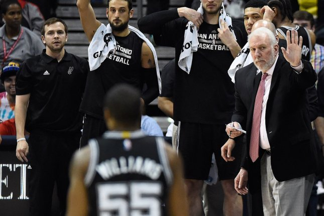 San Antonio Spurs head coach Gregg Popovich (R) holds forward Reggie Williams (55) from shooting as time expires against the Atlanta Hawks during the second half of an NBA game at Philips Arena in Atlanta, March 22, 2015. San Antonio won 114-95. Photo by David Tulis/UPI