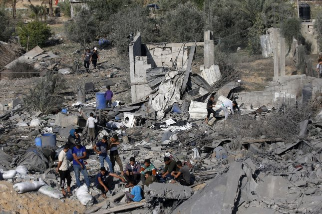 Palestinians check out the destruction following an Israeli airstrike at Deir al-Balah in the southern Gaza, on Thursday before a cease-fire took hold. Photo by Ismael Mohamad/UPI
