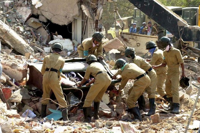 Uniformed rescue workers in Ahmedabad, India, clear debris left from a Jan. 26, 2001, earthquake that killed an estimated 20,000 people. (This picture was taken three days after the quake.) UPI/File
