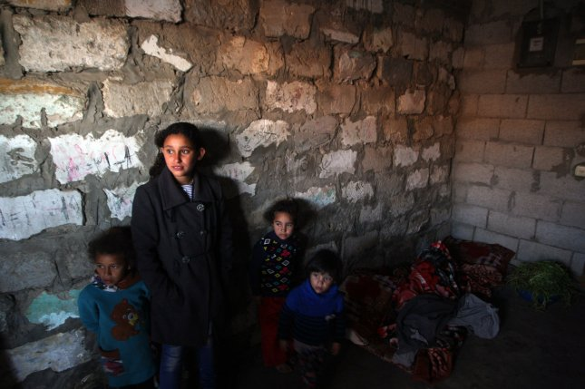 A woman and her children stand inside a refugee camp in Khan Younis, Gaza, where poverty has grown in recent years. Monday's survey drew a correlation between family size and those who are least able to afford basic survival needs. File Photo by Ismael Mohamad/UPI