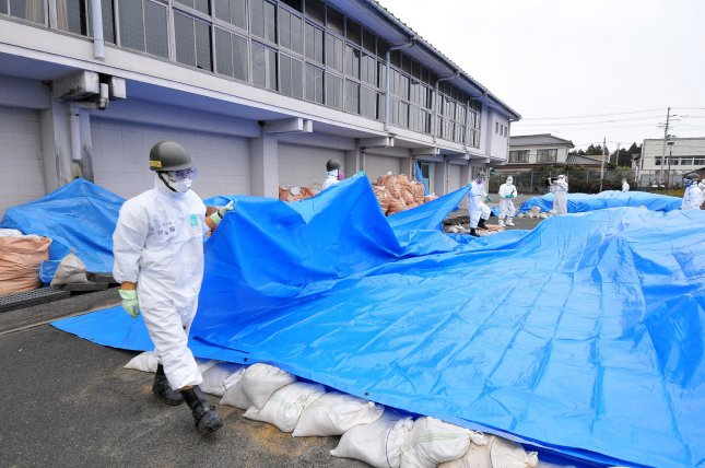 Member of Japan's Ground Self Defense Force decontaminate at the city office of Namie Machi, 8 kilometers from the Fukushima Dai-ichi nuclear power plant in Fukushima prefecture, Japan, on December 8, 2011. About 900 members of Japan's GSFD started a two-week decontamination operation. UPI/Keizo Mori