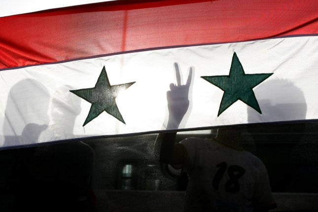 A Syrian protester gestures victory signs behind their national flag as they shout slogans calling for Syria's President Bashar al-Assad to step down during a protest in front of the Syrian embassy in Amman April 17, 2011. UPI