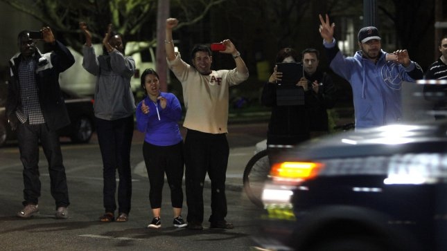 Neigbors wave and cheer on the Police as they stream past them on Arsenal Street moments after the last of the two Boston Marathon bombing suspects was caught in Watertown, Massachusetts on April 19, 2013. Monday's Boston Marathon bombing left three dead and over170 injured. UPI/Matthew Healey
