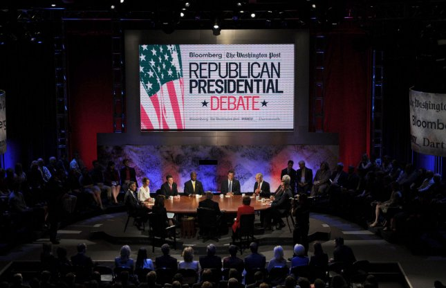 Flanked by large images of former President Ronald Reagan, the 2012 Republican presidential candidates speak during a presidential debate sponsored by Bloomberg and The Washington Post held at Dartmouth College in Hanover, New Hampshire, U.S., on Tuesday, Oct. 11, 2011. The event moderated by U.S. television talk show host Charlie Rose and featuring eight Republican candidates, presents the first debate of the 2012 political season focused solely on the economy. UPI/Daniel Acker/Pool
