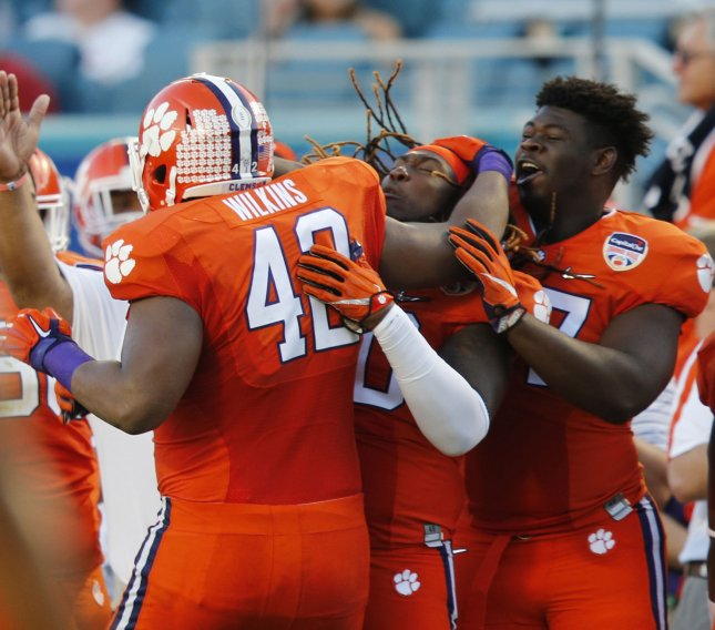 Christian Wilkins of the Clemson Tigers celebrates with teammates during a game against the Oklahoma Sooner. Photo by Pierre DuCharme/UPI