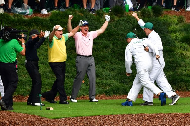Jack Nicklaus' caddie and grandson G.T. Nicklaus (R) celebrates after hitting a hole-in-one on the ninth hole during the Par 3 Contest at the 2018 Masters Tournament at the Augusta National Golf Club in Augusta, Ga., on Thursday. Photo by Kevin Dietsch/UPI