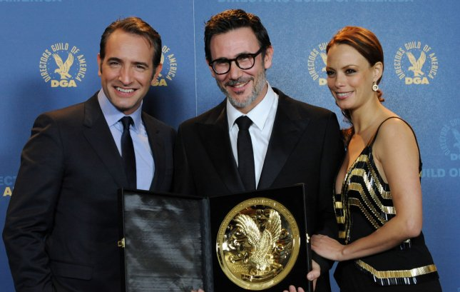 Michel Hazanavicius, director of The Artist, celebrates backstage with his award for outstanding directorial achievement in feature film with cast members Jean Dujardin (L) and Berenice Bejo at the 64th annual Directors Guild of America Awards in Los Angeles on January 28, 2012. UPI/Jim Ruymen