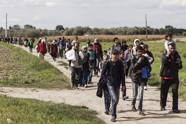 Refugees walk to the Reszke crossing in Hungary on the border with Serbia on September 8, 2015. Syrian and other refugees were sleeping for days in the fields waiting their chance to get a bus that will take them to a registration center nearby. File Photo by Achilleas Zavallis/UPI